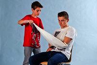 Ziehe nun ein Ende des Dreiecktuches vorsichtig unter den verletzen Arm bis zur Schulter.